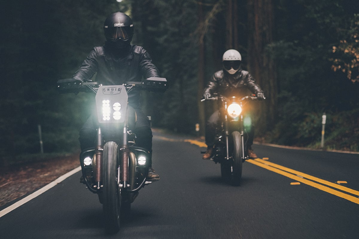 two motorcycles drive down road
