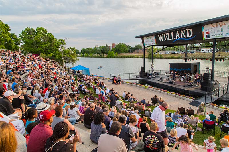 crowd listens to band at floating bandstand - Merritt Park Amphitheatre